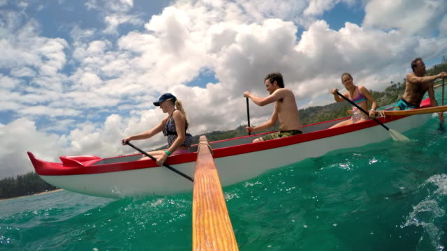 side view from outside outrigger canoe of four people paddling - タートル湾点の映像素材/bロール