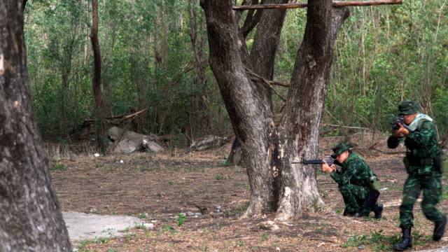 side view: Fully Equipped and Armed Soldier using tree as shield and going to the enemy