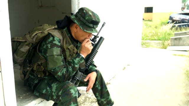 side view: Fully Equipped and Armed Soldiers is under stress and smoking