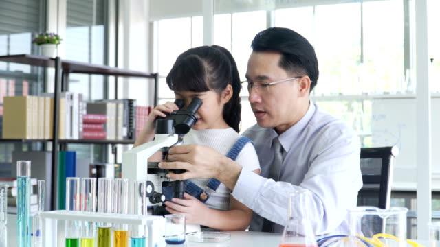 サイドビュー: 少女の興奮を感じるし、喜んでジェスチャーを示すとき彼女彼の教師を顕微鏡で発見 - chemistry点の映像素材/bロール