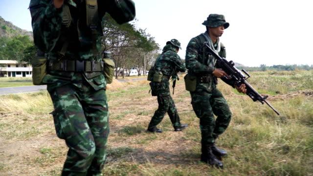 seitenansicht: gruppe von voll ausgerüstet und bewaffnet soldat praxis zu patrouillieren auf wiese - öffentlicher auftritt stock-videos und b-roll-filmmaterial