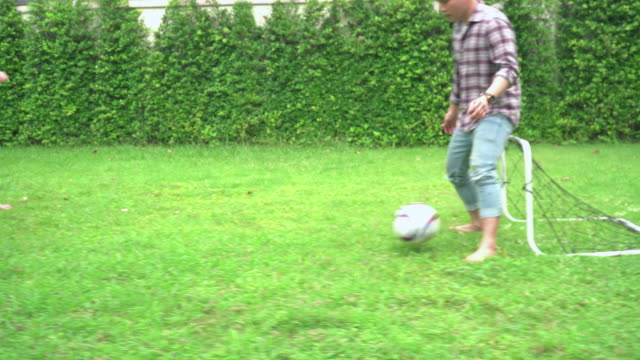 side view: group of young asian men playing soccer football for outdoor exercise and having leisure activity in their garden at the weekend.  family with two children,  younger brother send the ball to a sibling for kicking ball goal. - family with two children stock videos & royalty-free footage