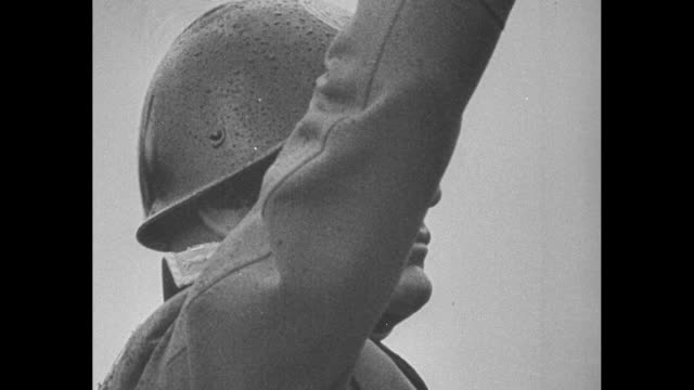 vídeos de stock, filmes e b-roll de side view cu italian prime minister benito mussolini wearing military helmet raises his arm to give fascist salute / italian troops parade in... - benito mussolini