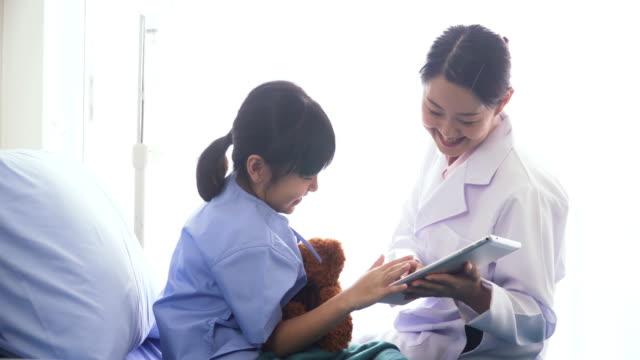 サイドビュー: デジタル タブレットの病棟でタイの女の子と話して日本の医師 - 女医点の映像素材/bロール