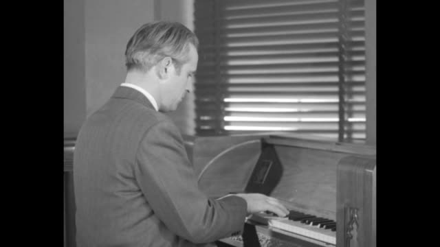 Side view man in suit plays carillon keyboard under Venetian blinds as he sits inside the Empire State Building VO music