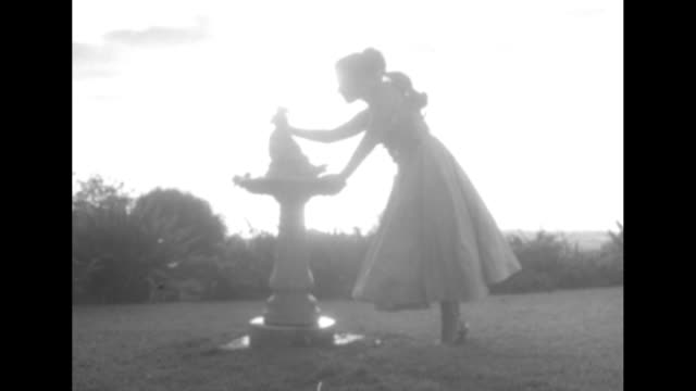 Side view model partly silhouetted against bright sky wearing in oneshouldered cocktail dress top covered with anthurium standing at a fountain / CU...