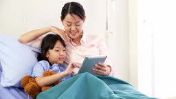 side view: Mother is belong to Japanese girl with a digital tablet in the hospital ward