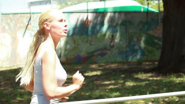 vídeos de stock, filmes e b-roll de a moving side view of a woman jogging down a road looking around her - olhando ao redor