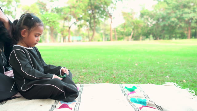 side view:  muslim asian teenage girl wearing a religious dress called hijab with feeling love and happiness from mother sitting on the carpet at public park for weekend activities. the concept of religious people having a picnic with positive emotion. - religious dress stock videos & royalty-free footage