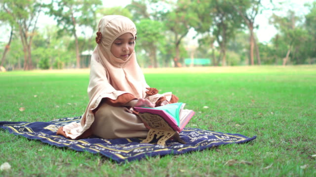 side view: muslim asian teenage girl wearing a religious dress with feeling love and happiness, sitting and reading koran on the carpet at public park for weekend activities. the concept of religious people having a picnic with positive emotion. - religious dress stock videos & royalty-free footage