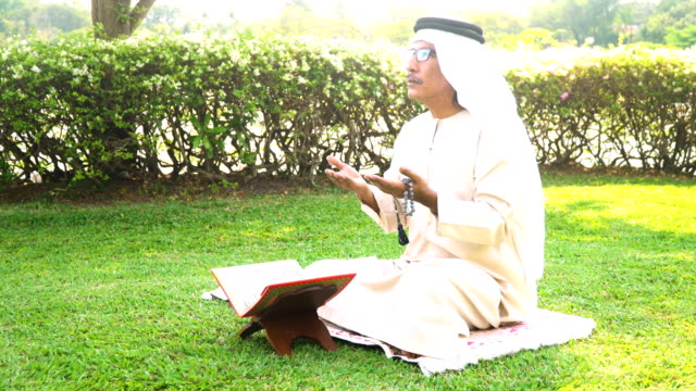 side view: muslim grandfather read quran in public park in morning - koran stock videos and b-roll footage