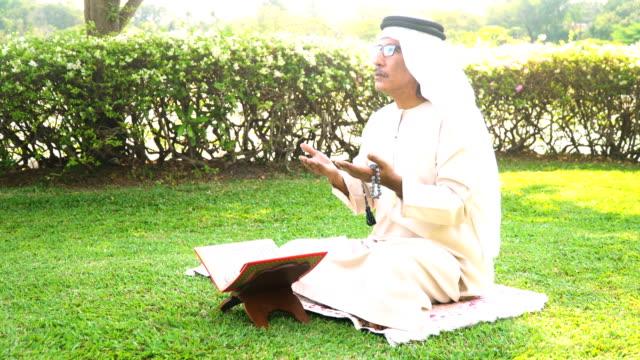 side view: muslim grandfather read quran in public park in morning - koran stock videos & royalty-free footage