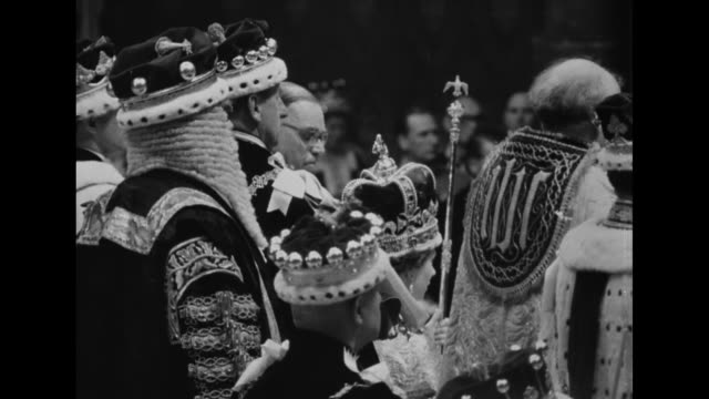 Side view newly crowned Queen Elizabeth II surrounded by peers wearing elaborate robes and crowns / Peers wearing coronation costumes and crowns