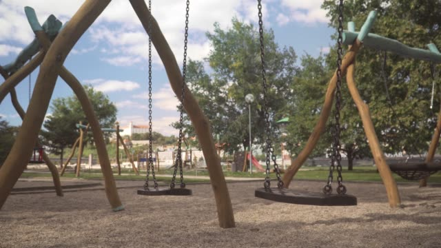 side view: no children on a swing in a public playground or schoolyard, bratislava along danube river on a sunny day in summer of slovakia. concept of outdoor play equipment with a feeling of loss, violence, and loneliness. - missing people stock videos & royalty-free footage