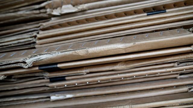 stockvideo's en b-roll-footage met zijaanzicht van een gegolfde kartonnen stapel in een recycling centrum - karton