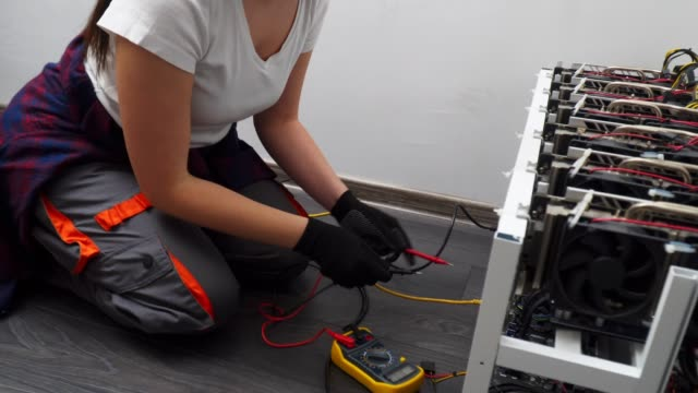 Side view of a Female Electrician Working on an IT item, Engineering, Measuring Electrical Resistance, Professional IT Support, Technology, STEM, Experienced Professional