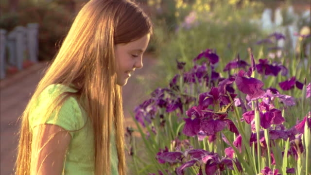 Side view of a girl watching and trying to hold a butterfly among iris flowers.