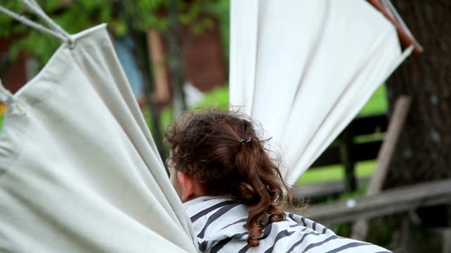 vídeos de stock e filmes b-roll de side view of a little girl hanging on the hammock in the backyard - inclinar se pose