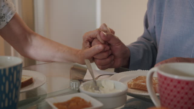 side view of a mature couple holding hands and doing breakfast together - wedding ring stock videos & royalty-free footage