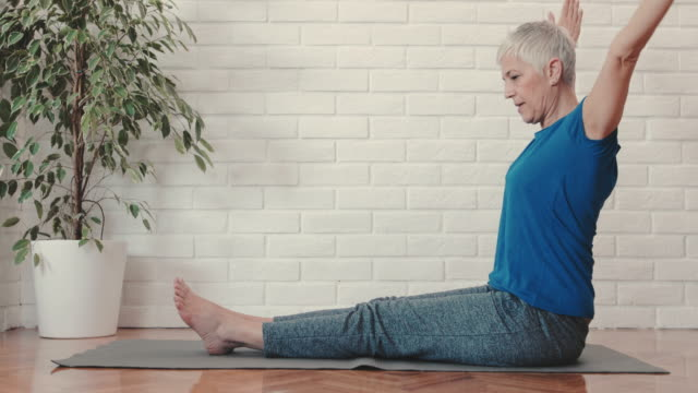 side view of a mature woman doing stretching exercises at home. - stretching stock videos & royalty-free footage