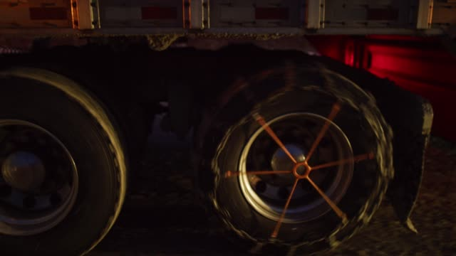 side view of a semi truck's wheels and tires outfitted with snow chains at night - chain stock videos & royalty-free footage