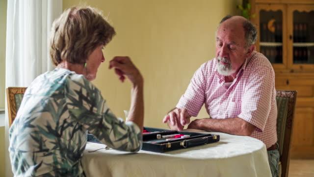 Seitlicher Blick auf ein älteres Paar, ein Brettspiel - soziale Senioren