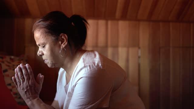 自宅で祈る先輩女性のサイドビュー - カトリック点の映像素材/bロール