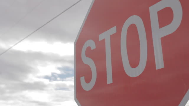 side view of a stop sign blowing in the wind. - stop sign stock videos and b-roll footage