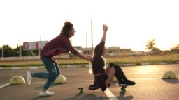 Side view of a woman with her hands raised up sitting on a longboard while her friend is pushing her behind and running during sunset. Enjoying life. Lens flare. Slowmotion shot