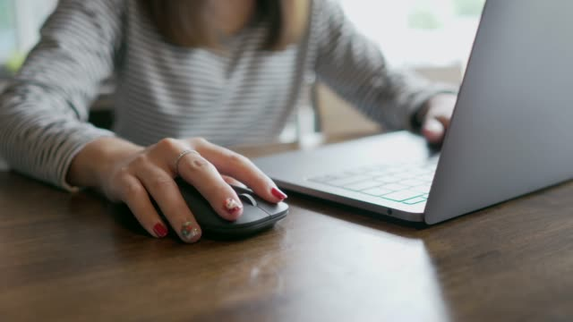 side view of a woman's hand using wireless mouse on the wooden table in cafe - computer keyboard stock videos & royalty-free footage
