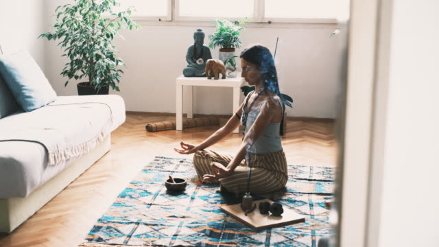 side view of a young woman  sitting in a lotus position while meditating at home - mudra stock videos & royalty-free footage
