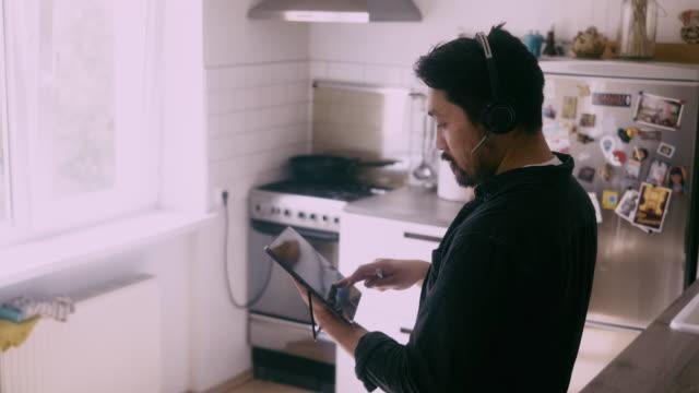 seitenansicht eines asiatischen mannes verwendet digitales tablet während der telefonkonferenz - arbeiten von zuhause stock-videos und b-roll-filmmaterial