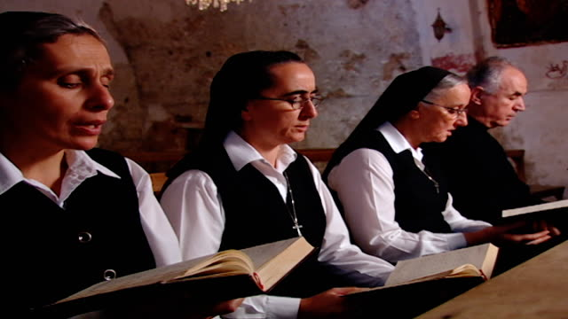 side view of antonine nuns and a priest singing a hymn in arabic in our lady of our lady of qannoubine monastery which served as a fortress for... - nun stock videos & royalty-free footage