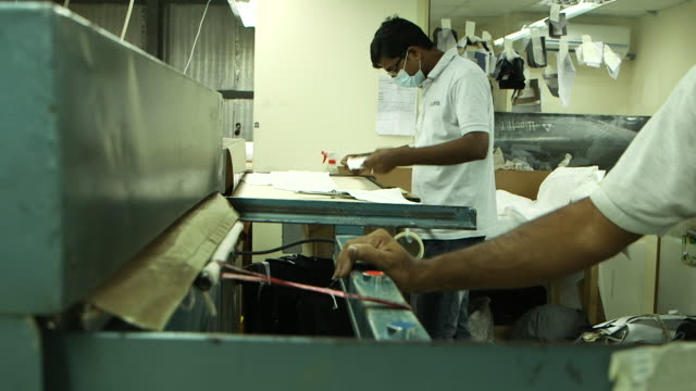 side view of asian tailors working in a garment factory. - jiddah stock-videos und b-roll-filmmaterial