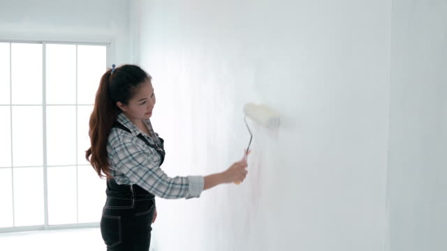 side view of asian woman with paint roller painting wall in her new house. - paint roller stock videos & royalty-free footage