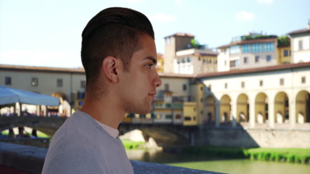 side view of attractive latin male standing near ponte vecchio bridge - ponte点の映像素材/bロール