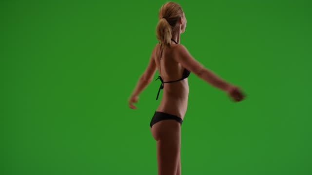 vídeos y material grabado en eventos de stock de side view of attractive young woman spinning on green screen - accesorio de cabeza