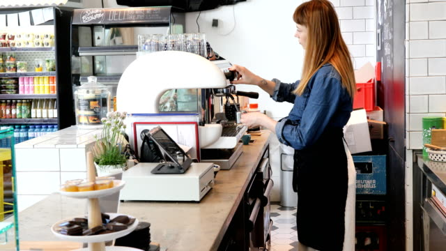 Side View Of Barista Preparing Coffee At Cafeteria