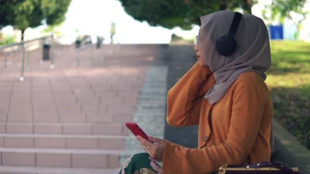seitenansicht der schönen asiatischen mädchen hören podcast im park - religiöse kleidung stock-videos und b-roll-filmmaterial