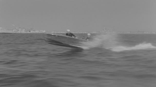 WS Side POV View of Boat speeding through harbor back right two sailors in speed boat