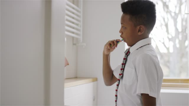 side view of boy brushing his teeth at home in his bathroom - uniform stock videos & royalty-free footage