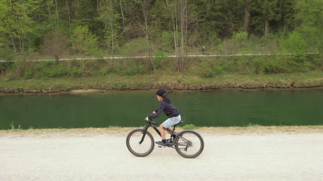 side view of boy cycling next to a river. - 8 9 years stock videos & royalty-free footage