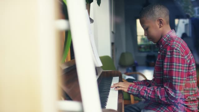 side view of boy playing piano at home - piano stock videos & royalty-free footage