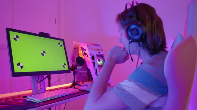 side view of caucasian young man, a gamer, streamer talking to audiences while playing a multiplayer online game, live streaming on computer pc, screen show green screen,  positive emotion in the multicolor decorated room as cyberpunk - game show stock videos & royalty-free footage