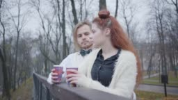 Side view of charming Caucasian girl with red hair talking to stylish boy with long hair. Young couple dating in autumn park. Unusual boyfriend and girlfriend standing at the bridge with hot tea.