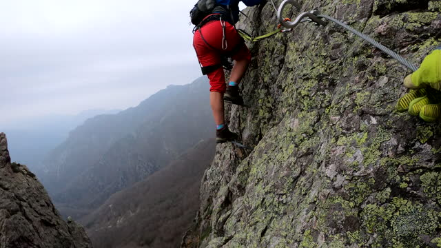 side view of climbers ascending a metal ladder above a valley - ridge stock videos & royalty-free footage