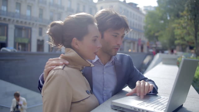 CU Side View of Couple using laptop outside / Toulouse, Haute Garonne, France