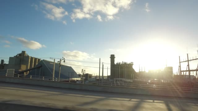 side view of driving at sunrise passing power station - romantic sky stock videos & royalty-free footage