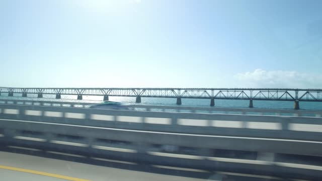 vídeos de stock, filmes e b-roll de side view of driving on beach highway in a sunny day - side view