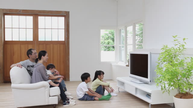 WS Side view of family with baby boy (12-17 months) and son (8-9) and daughter (8-9) watching TV in living room / Setagaya, Tokyo, Japan